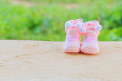 Pink knitted socks for baby girl on the wooden, on green backgro Stock Image