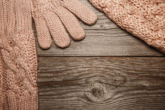 Pink knitted warm gloves, hat and sharf on old texture background. Pink knitted warm gloves, hat and sharf on old rustic Wooden texture background royalty free stock image