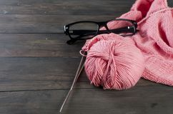 Knitting threads and glasses  on a wooden table. Royalty Free Stock Photos