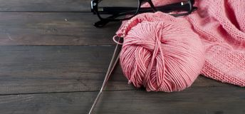 Knitting threads and glasses  on a wooden table. Stock Images