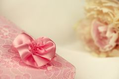 Pink lace gift box with an ivory peony. In the background Stock Photo