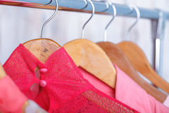 Pink lace women`s blouse on hangers on rack in fashion store. v. Pink lace women`s blouse on wooden hangers on a rack in a fashion store. vivid women`s closet stock photo