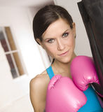 Pink Gloves Lady Boxer Stands at Heavy Bag Stock Photography