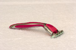 Pink lady shaver on a towel. Pink lady shaver on a white towel stock photo