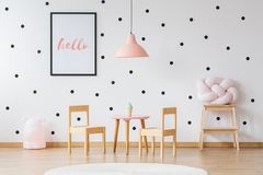 Pink lamp in girl`s room. Pink lamp above wooden table with chairs in girl`s room with wallpaper with black dots Stock Image