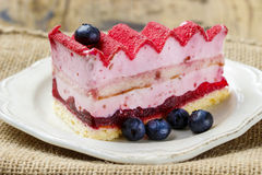 Pink layer cake decorated with fresh fruits Royalty Free Stock Photos