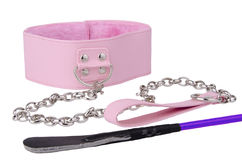 Pink leather collar and riding crop Royalty Free Stock Photos