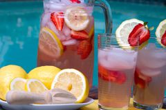 Pink lemonade. Two glasses of home made iced cold pink strawberry lemonade and pitcher on hot summer on edge of swimming pool Stock Images