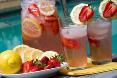 Pink lemonade. Two glasses of home made iced cold pink strawberry lemonade and pitcher on hot summer on edge of swimming pool Royalty Free Stock Photo