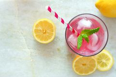 Pink lemonade with mint and lemons, overhead view on marble Royalty Free Stock Photos