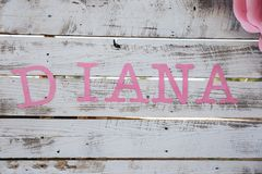 Pink letters name Diana on white wodden wall, Baby shower Stock Photos