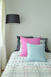 Pink and light blue pillow on single bed with black shade standi. Ng lamp at home Royalty Free Stock Image