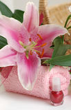 Pink Lilies in Spa. Closeup of a pink lily on a pink towel and a nail polish Royalty Free Stock Image
