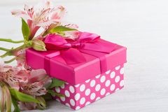Pink lilly flowers with gift box. Greeting card concept Royalty Free Stock Image