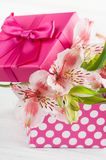 Pink lilly flowers with gift box. Greeting card concept Stock Photography