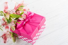 Pink lilly flowers with gift box. Greeting card concept Stock Photo