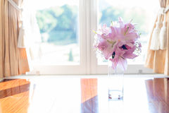 Pink Lily flower in glass jar placed by the elegant window Royalty Free Stock Photography