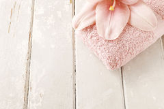 Pink lily flower and soft towel on wooden background. Copy space royalty free stock photography