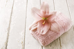 Pink lily flower and soft towel on wooden background. Copy space stock photos