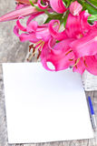 Pink lily Robina flowers bouquet and blank paper sheet with pen Stock Photos