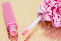 Pink lipgloss with flower petals Royalty Free Stock Photos