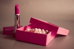Pink lipstick and box with pearls on a beige background. Box with pearls and pink lipstick on a beige background Stock Image