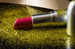 Pink lipstick and golden specks of glitter dust. Fancy and glamour photograph of a lipstick with ribbon and golden specks of glitter dust on a smooth black Stock Photos