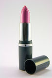 Pink Lipstick with Lid. Single pink lipstick in a grey container and lid on a plain background Royalty Free Stock Image