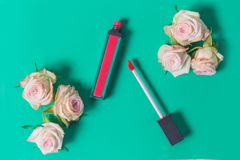 Pink lipstick, lip gloss, open, with delicate pink shrub roses at the edges in bright turquoise, green background, close-up, profe. Pink lipstick, lip gloss Stock Image