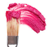 Pink lipstick stroke (sample) with makeup brush. Isolated on white stock photography