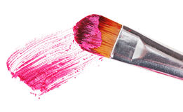 Pink lipstick stroke (sample) with makeup brush. On white Stock Image