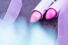 Pink lipsticks & flower in the foreground Stock Photography