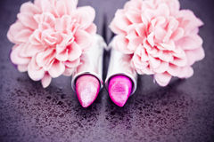 Pink lipsticks and flower petals Stock Images