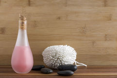 Pink Liquid Soap with White Body Scrubber and Black Rocks Royalty Free Stock Images
