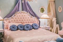 Pink little princess room with satin pillows, bedside lamps, bedside tables, frames on the walls. Luxury rich bedroom interior.  royalty free stock photo