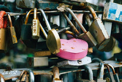Pink lock between other closed locks Stock Photography