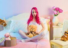 Pink Long Haired Woman Sitting on Double Bed With Bear Plsuh Toy at Daylight Royalty Free Stock Image