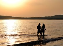 Pink love. Lovers walking in the sunset Stock Photos