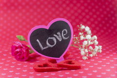 Pink Love chalkboard sign with flowers on romantic heart pattern Royalty Free Stock Images