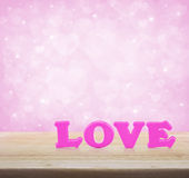 Pink love word on wooden table over light pink heart blur backgr Royalty Free Stock Images