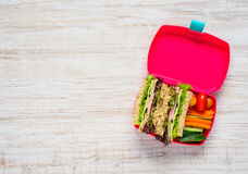 Pink Lunch Box with Sandwich and Copy Space. Top View of Pink Lunch Box with Sandwich and Vegetables Stock Photos