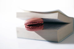 Pink macaron. In an opened book Stock Images
