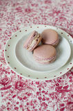 Pink macarons. Delicate and elegant wedding pink macaroons with white cream on floral background Royalty Free Stock Photos
