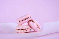 Pink macarons petit fours cookies close up. On pink background Stock Photos