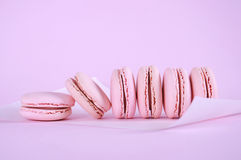 Pink macarons petit fours cookies in a row. Pink macarons petit fours cookies close up on pink background Royalty Free Stock Photography