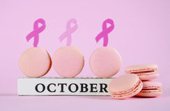 Pink macarons for Pink Ribbon October charity month with symbols. Stock Images