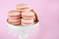 Pink macarons on white vintage style cake stand - close up. Royalty Free Stock Photo