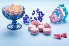 Pink Macaroons cakes with colorful fluffy marshmallows in blue vase. royalty free stock photo