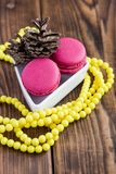 Pink macaroons with christmas decorations on wooden background Stock Images