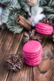 Pink macaroons with christmas decorations on wooden background Stock Photography